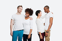 Two young couples in casuals standing together over white background