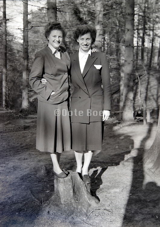 two happy smiling adult women standing on top of the stump of a cut tree Netherlands 1950s