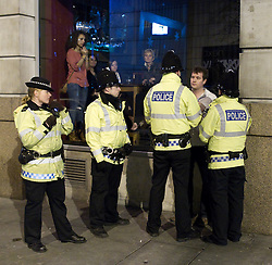 """© licensed to London News Pictures. Manchester, UK 17/12/2011. Police detain a man outside a nightclub as those inside look on. Despite freezing temperatures, """"Mad Friday"""" revellers in Manchester enjoy what is traditionally the busiest night of the year for emergency services, before Christmas. Photo credit: Joel Goodman/LNP"""