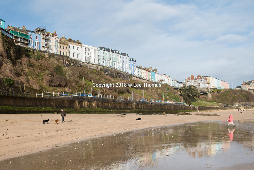 Tenby, Pembrokeshire, Wales, UK. 11th March 2018. A bright and seasonally warm start to the day at Tenby harbour as early beach walkers and dog owners make the most of the weather. // Lee Thomas, Tel. 07784142973. Email: leepthomas@gmail.com  www.leept.co.uk (0000635435)