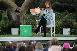 """WASHINGTON, DC - APRIL 02: (AFP OUT) U.S. first lady Melania Trump reads the book """"You,"""" by Sandra Magsamen during the 140th annual Easter Egg Roll on the South Lawn of the White House April 2, 2018 in Washington, DC. The White House said they are expecting 30,000 children and adults to participate in the annual tradition of rolling colored eggs down the White House lawn that was started by President Rutherford B. Hayes in 1878. (Photo by Chip Somodevilla/Getty Images)"""