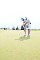 Full length of couple playing golf at course against clear sky