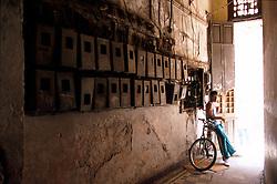 A boy escapes from the heat in the corridor of a rundown apartment building in Havana, Cuba. (Photo © Jock Fistick)