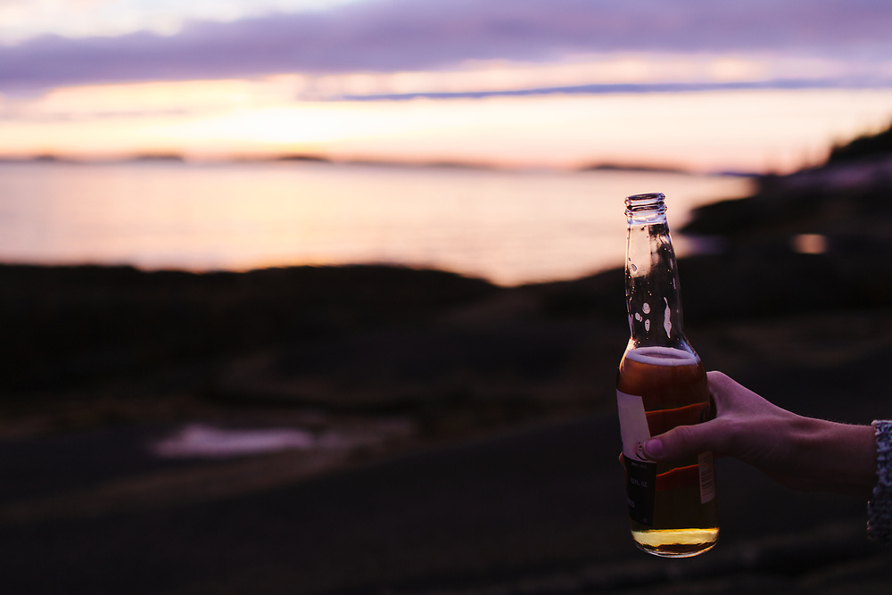 Young woman drinking beer in front of ocean.