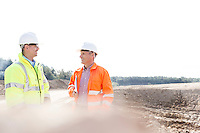 Smiling engineers discussing at construction site on sunny day