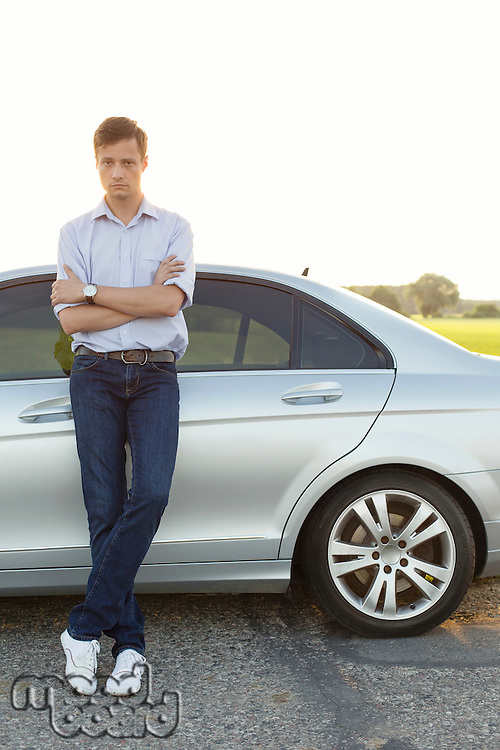Full length portrait of young man standing by car at countryside