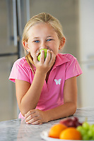 Girl eating apple in kitchen