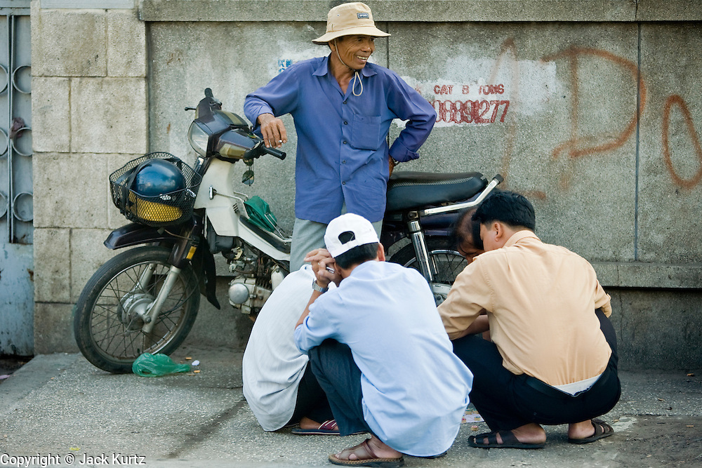 08 MARCH 2006 - HO CHI MINH CITY, VIETNAM: Men on a sidewalk play a board game while a friend leans against a motorcycle in Ho Chi Minh City, Vietnam. HCMC is still widely known as Saigon. PHOTO BY JACK KURTZ