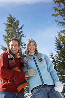 Couple wearing winter clothing standing on hillside low angle view portrait