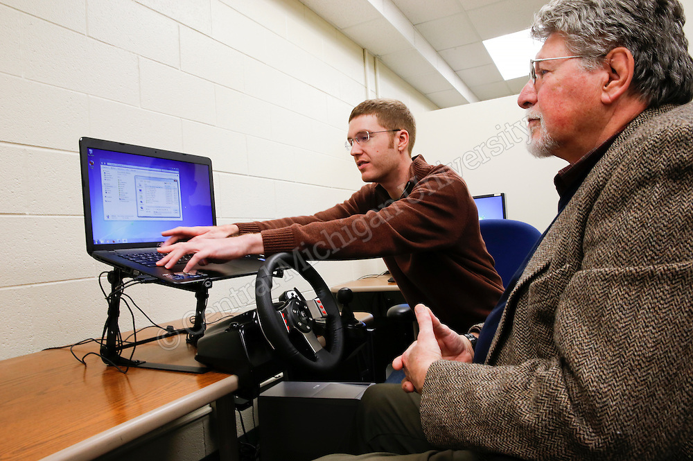 Alexander Bos, Grand Rapids, Psychology graduate assistant (left), get Jim Malone Beach ready to do a test drive at the CMU Driving Evaluation, Education and Research Center. Photo by Steve Jessmore/Central Michigan University
