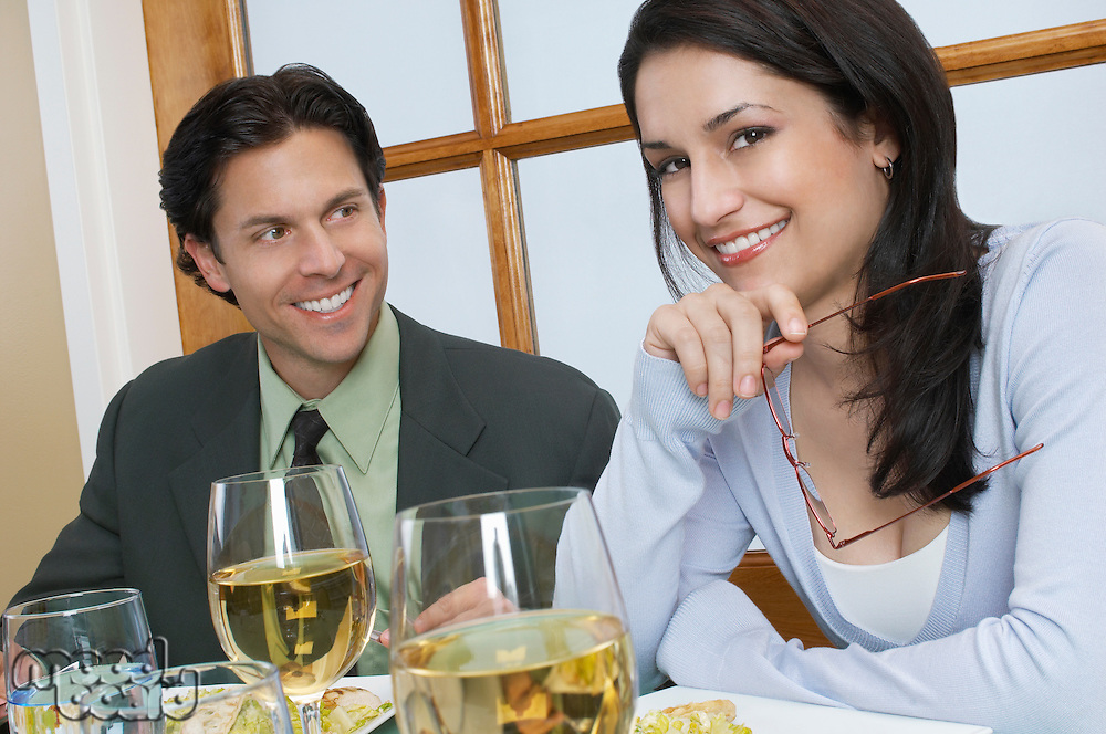 Mid adult couple at restaurant table, woman looking at camera