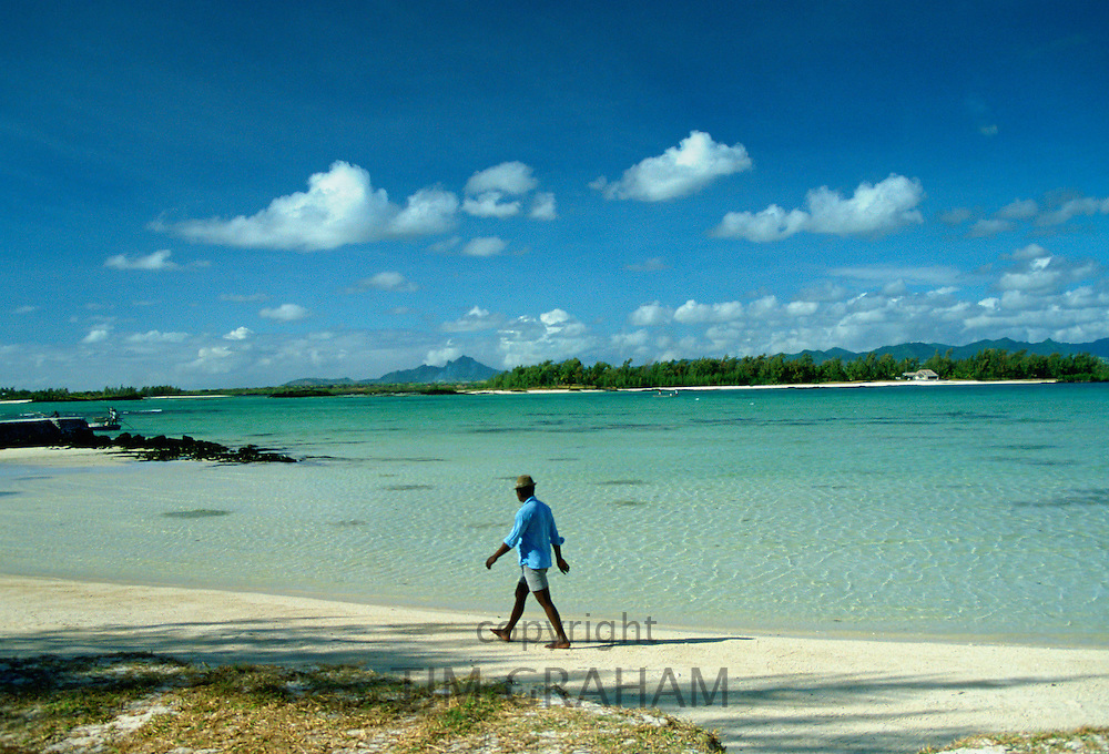 Man walking alone one the beach in Mauritius