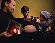 "FIRST CONTACT: ""FETALFONE"" Photo Illustration for the Future of Communication GEO (Germany) Special Issue. Fictional Representation and Caption: The Smith's of Vallejo, California were not certain that the latest hi-tech form of giving their (unborn) child a headstart was effective, but it sure was fun to see Junior react to their voice on his ""fetalfone"". It was true that the youngster could only use it to listen (even if he could talk, it would very difficult in the amniotic fluid), but they enjoyed the idea that their offspring would be comfortable with a cell phone from Day Minus-90 to Day One when he popped out. The flat screen imaging unit affords the parents (and in this case older sister) the opportunity to track the unborn's development and also watch his reactions when they talk to him on the ""Fetalfone"". [Fetus with ""Fetalfone"" shown on ""Babewatch"", fetus-scan home imaging system can be monitored by absent parent via Internet.] MODEL RELEASED."