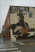 People walk into the Woody Guthrie Center in the Brady District on Friday, October 18, 2013, in Tulsa, Oklahoma. A large mural of Woody Guthrie is painted on the side of the museum.<br /> <br /> http://www.thebradyartsdistrict.com/<br /> http://woodyguthriecenter.org/