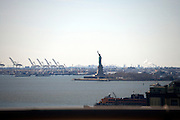 Statue of Liberty in New York City and harbor with the port of New Jersey in the background