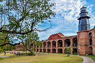 Inside historic Fort Jefferson, a group of people sit in the courtyard, beginning a guided tour with a park ranger. Features of this establishing shot include a tree, the brick wall and arches of the historic military fort, and black lighthouse on the roof seta against blue sky.
