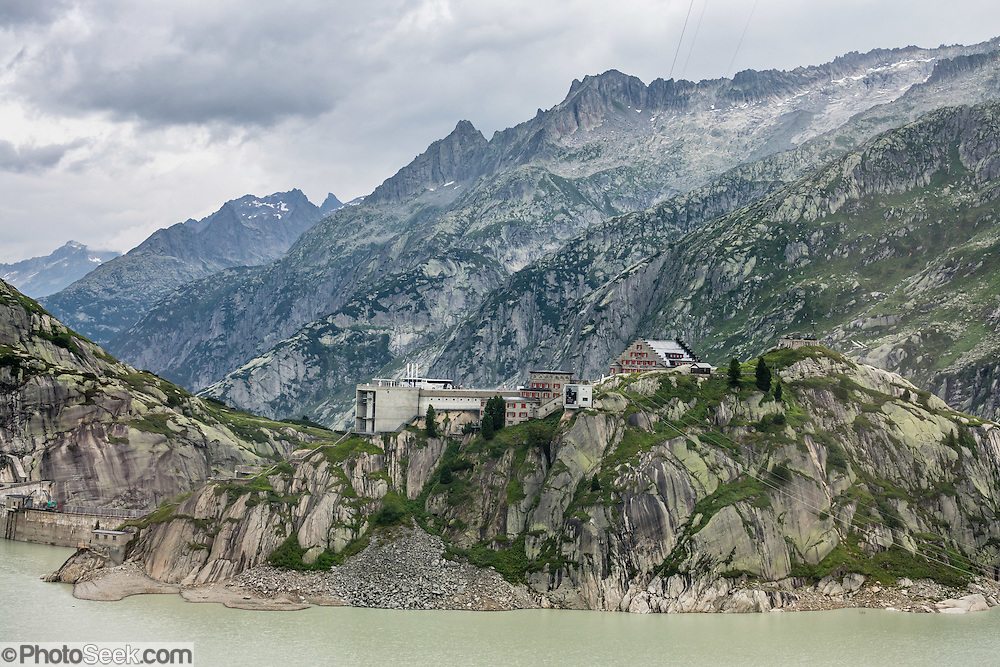 Ride the PostBus from Meiringen, over Grimsel Pass to Oberwald, in the Bernese Alps, Switzerland, Europe. An extensive system of hydro-electric dams built in the 1920s and 1950s dominates the scenery of Grimselpass. Some aging hotels cling to the pass.