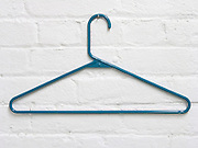 clothes hanger hanging against a white painted masonry wall