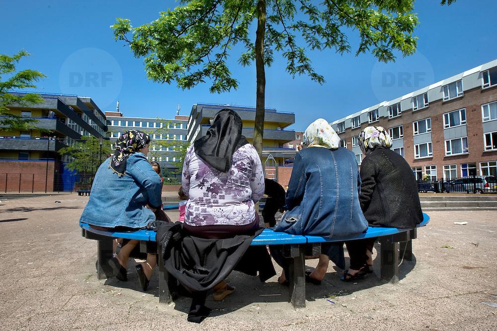 Nederland Rotterdam 24-05-2009 20090524 Foto: David Rozing .                                                                                    .Achterstandswijk Bloemhof, groepje moslima's zitten op pleintje op bankje onder boom Muslim woman chatting outside in neighbourhoud, muslims, straatbeeld, stadbeeld.Foto: David Rozing
