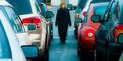 a woman is abstracted by motion blur walking  between two rows of vehicles at the Bainbridge Island, Washington ferry termimal. panorama