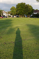 Suburban park in Dublin Ireland, woman's shadow on grass
