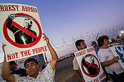 "23 JUNE 2012 - PHOENIX, AZ:  People picket the front of the Maricopa County Jail in Phoenix Saturday. About 2,000 members of the Unitarian Universalist Church, in Phoenix for their national convention, picketed the entrances to the Maricopa County Jail and ""Tent City"" Saturday night. They were opposed to the treatment of prisoners in the jail, many of whom are not convicted and are awaiting trial, and Maricopa County Sheriff Joe Arpaio's stand on illegal immigration. The protesters carried candles and sang hymns.      PHOTO BY JACK KURTZ"