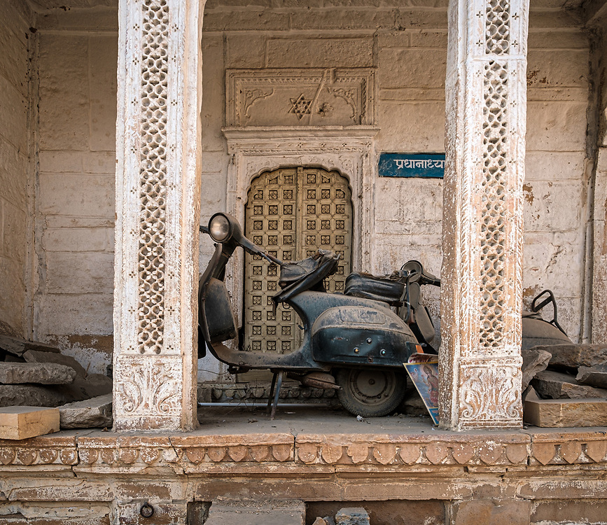 """JAISALMER, INDIA - CIRCA NOVEMBER 2018: Abandoned Motorbike in Jaisalmer.  Jaisalmer is also called """"The Golden City, and it is located in Rajasthan. . The town stands on a ridge of yellowish sandstone, and is crowned by the ancient Jaisalmer Fort."""