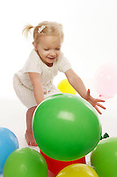 Two year old toddler chases a green balloon in studio celebrating a birthday.