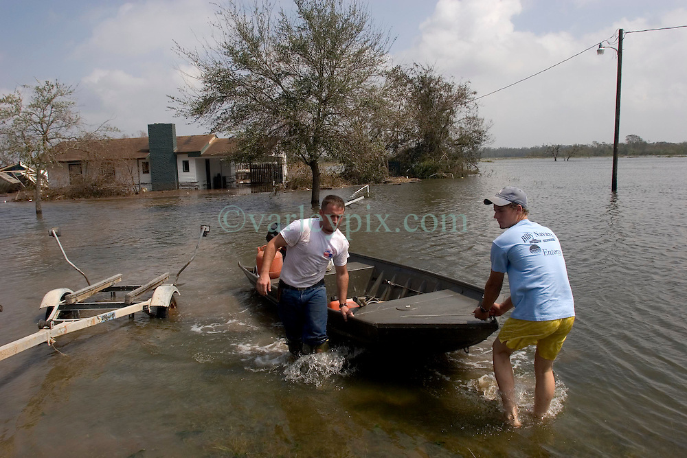 25 Sept, 2005.  Carlyss, Louisiana.  Hurricane Rita aftermath. <br /> Local cajun man Aaron Stokes and friend Chase Reider put in their boat to tour the swamps and bayou's checking on neighbours and their homes.<br /> Photo; &copy;Charlie Varley/varleypix.com