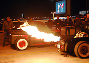 A crowd of guys watching the flames coming out of the exhaust pipe of a customised Hotrod, Viva Las Vegas Festival, Las Vegas, USA 2006