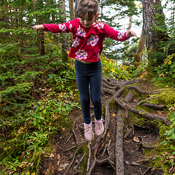 A young girl jummps while hiking on a trail at Quoddy Head State Park in Lubec, Maine.