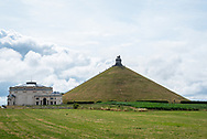 "De Leeuw van Waterloo (Frans: Butte du Lion) is een herdenkingsmonument voor de Slag bij Waterloo (18 juni 1815) dat op initiatief van koning Willem I van het Verenigd Koninkrijk der Nederlanden werd opgericht. Het monument staat op het grondgebied van de gemeente Eigenbrakel in de Belgische provincie Waals-Brabant.[1] Het monument bestaat uit een reusachtige gietijzeren leeuw die op een kunstmatige heuvel 45 meter boven de omringende vlakte uittroont. Foto: Gerrit de Heus   The Lion's Mound (French: Butte du Lion, lit. ""Lion's Hillock/Knoll""; Dutch: Leeuw van Waterloo, lit. ""Lion of Waterloo"") is a large conical artificial hill located in the municipality of Braine-l'Alleud (Dutch: Eigenbrakel), Belgium. King William I of the Netherlands ordered its construction in 1820, and it was completed in 1826. It commemorates the location on the battlefield of Waterloo where a musket ball hit the shoulder of William II of the Netherlands (the Prince of Orange) and knocked him from his horse during the battle.[1] It is also a memorial of the Battle of Quatre Bras, which had been fought two days earlier, on 16 June 1815. Photo: Gerrit de Heus"