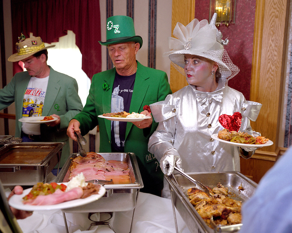 Celebrity Dinner with the Munchkins, Chittenango, NY, 2005..Fans of the Wizard of Oz movie wear costumes inspired by the 1939 movie while serving themselves at the buffet line at the 2005 Ozfest celebrity dinner with the munchkins.  Jane Craddock, right, wears an outfit inspired by the character, the Tin Woodsman.  Ozfest takes place in Chittenango, NY where Oz creator L. Frank Baum was born...Photo by Susana Raab.