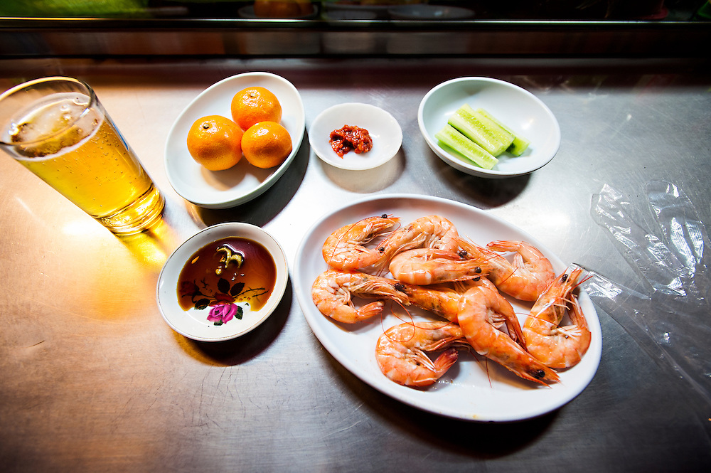 Shrimp served with soy sauce and wasabi, cucumbers with red pepper paste, mandarin oranges, and beer, at a pojangmacha next to Lotte Department Store and Hotel in Seomyeon, Busan, South Korea.