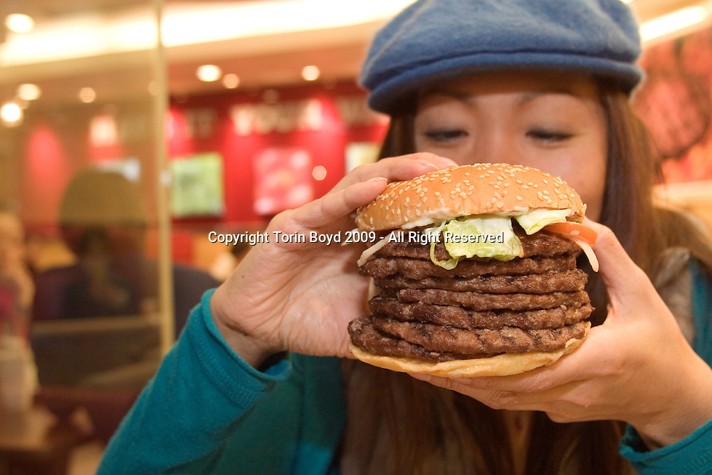 "This is the ""Windows 7 Whopper"", a seven layer beef patty hamburger being sold for a limited time only at all Burger King outlets in Japan. This is a special campaign to commemorate the release of Windows® 7, Microsoft's new operating system. Both the hamburger and operating systems were released on October 22, 2009, and according Burger King Japan (BKJ) the idea for this promotional campaign originated by Microsoft. As for sales of this mega burger in a land where fresh fish and healthy diets are the norm, the Windows 7 Whopper has been a huge success. So much that the campaign has been extended an additional week to November 6, 2009. To date, October 31, a total of 10,000 Windows 7 Whoppers have sold, more than doubling their original sales forecast of 4500 by this same date. The price of the burger is 1,450 yen or $16 USD (including tax), but they also offer the first 30 burgers at each outlet daily for 777 yen $8.60 USD. These first 30 quickly sell out with most customers lining up outside prior to opening hours to purchase the discounted burger. This Windows 7 Whopper campaign is only taking place in Japan where Burger King opertates fifteen outlets nationwide (and growing). The woman in the photo is Eri Hiraoka of Tokyo, sampling a Windows 7 Whopper at the Nishi Shinjuku Burger King outlet in Tokyo on October, 31, 2009...Nutritional facts: each Windows 7 Whopper contains 7 layers of beef patties and contains 2120 calories. It weighs a 950 grams (2.09 lbs), or nearly one kilo. As for fat content, a normal single patty Whopper contains 40 grams of fat, so the estimated fat content of the Windows 7 Whopper is an astounding 280 grams of fat, the same as  2.5 sticks of butter. The daily recommended fat intake for most is 30-35 grams of fat per day."