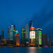 In the early evening the lights of Shanghai China come alive on the Bund overlooking the Huangpu River