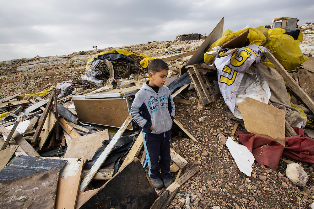 A boy examines the remains of his home destroyed by Israeli forces. Dec. 28, 2013. West Bank, Palestinian Territories. (Photo by Gabriel Romero/Alexia Foundation ©2014)