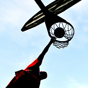 A basketball player dunks the ball at Bryan Park in Bloomington, Indiana.