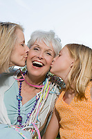Senior woman being kissed by daughter and granddaughter