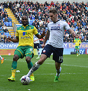 Dorian Dervite and Cameron Jerome during the Sky Bet Championship match between Bolton Wanderers and Norwich City at the Reebok Stadium, Bolton, England on 11 April 2015. Photo by Mark Pollitt.