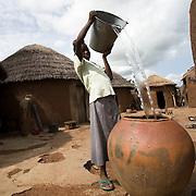 Mariam Alhassan, 11, pours the water she brought back from a borehole located 15 minutes away in a large clay container inside the compound where she lives with her family in the village of Ying, northern Ghana, on Monday June 4, 2007.