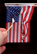 setting fire to an American flag against a black background