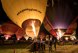 © Licensed to London News Pictures. 11/08/2016. Bristol, UK. Bristol International Balloon Fiesta 2016. Picture of the Night Glow on Thursday evening. Balloons are lit up with their burners, in rhythm to music. The Bristol International Balloon Fiesta is Europe's largest ballooning event and takes place from Thursday 11th August – Sunday 14th August, attracting half a million people over four days. This year 150 hot air balloons will attend, taking off in mass ascents at dawn and dusk. On Thursday and Saturday evenings, 30 balloons will tether in the main arena and light up in sequence to music for the famous Night Glows. Photo credit : Simon Chapman/LNP