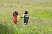 Two girls (7-9) holding hands running in field