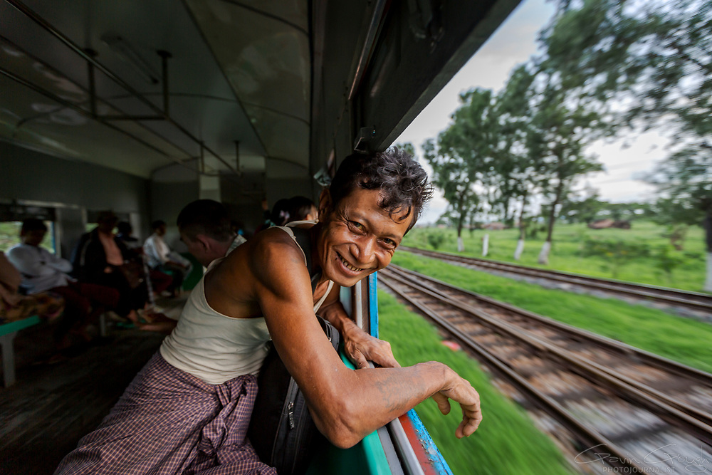 "A passenger leaning out of a window of the ""Circular Railway"" in Yangkok, Myanmar."
