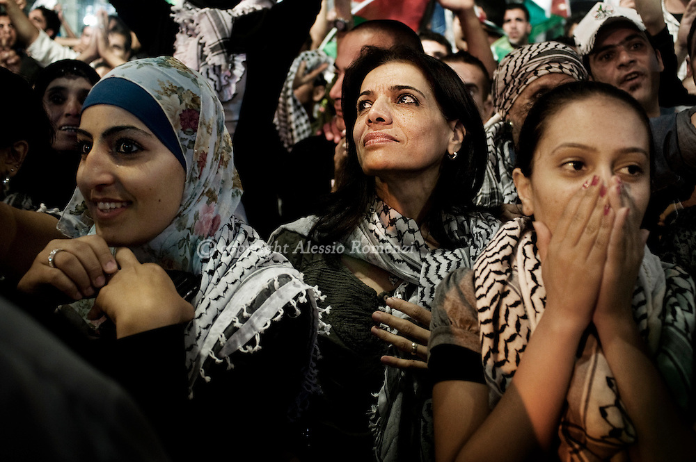 RAMALLAH : Palestinians gather to watch a wide screen relaying live footage of Mahmud Abbas' speech at the United Nations General Assembly in New York on September 23, 2011 in the West Bank city of Ramallah. ALESSIO ROMENZI
