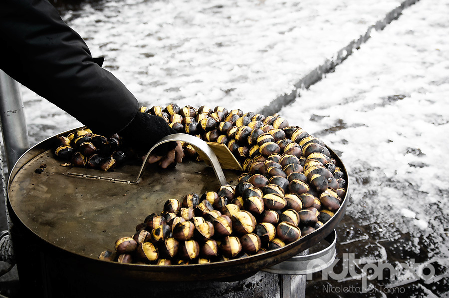 A man's hand ranges roasted chestnuts on top of the roaster while it is snowing all around