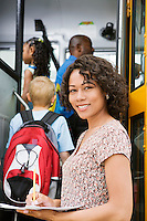 Teacher Loading Elementary Students on School Bus