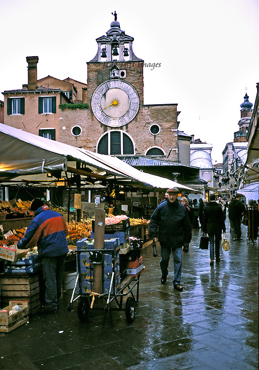 Rialto market, church of S. Giacomo, steps of Rialto Bridge in distance, on a rainy day, with shoppers and pedestrians walking by stalls of vegetables and fruits.