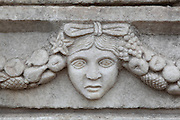 Mask and garland frieze from the Portico of Tiberius on the Southern portico of the Agora, 1st century AD, Aphrodisias, Aydin, Turkey. The Sculpture School at Aphrodisias was an important producer of carved marble sarcophagi and friezes from the 1st century BC until the 6th century AD. The Portico of Tiberius was built under the reign of Tiberius and has many examples of mask and garland friezes, consisting of the heads of gods, goddesses, theatrical characters, mythological figures or masks, each with a distinct facial expression, between hanging garlands of leaves, fruit and flowers. This example may represent madness. Aphrodisias was a small ancient Greek city in Caria near the modern-day town of Geyre. It was named after Aphrodite, the Greek goddess of love, who had here her unique cult image, the Aphrodite of Aphrodisias. The city suffered major earthquakes in the 4th and 7th centuries which destroyed most of the ancient structures. Picture by Manuel Cohen